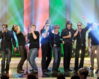 Neun Musiker auf der Bühne.